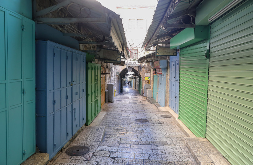 Stores are seen shuttered closed and streets are empty in Jerusalem's Old City amid Israel's third coronavirus lockdown, on January 4, 2021. (photo credit: MARC ISRAEL SELLEM/THE JERUSALEM POST)