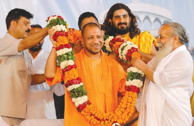 SUPPORTERS OF Yogi Adityanath (center), chief minister of India's most populous state of Uttar Pradesh, present him with a garland on the birthday of Nritya Gopal Das, a famous Hindu priest, in Ayodhya, in 2017. (photo credit: PAWAN KUMA/REUTERS)
