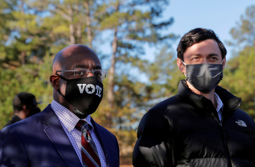 Democratic US Senate candidates Jon Ossoff and Rev. Raphael Warnock look on as they appear together at a campaign rally ahead of US Senate runoff elections in Augusta, Georgia, US, January 4, 2021. (photo credit: REUTERS/MIKE SEGAR)