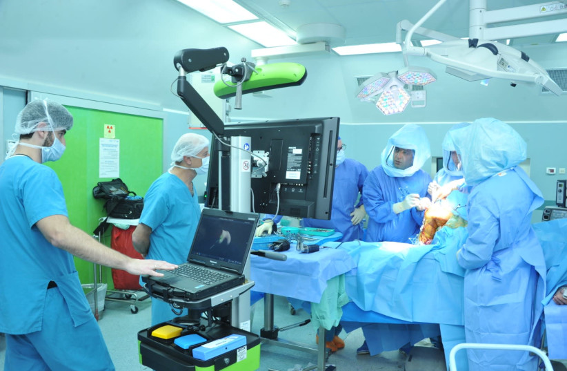 Doctors performing a surgery via the guidance of a robot.  (photo credit: Courtesy)