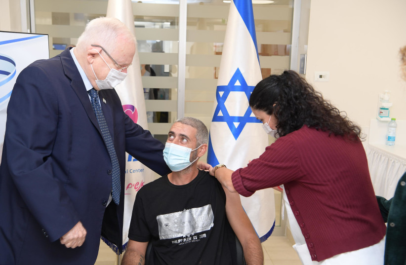 President Reuven Rivlin is seen alongside the first person to receive the second dose of the Israel-made coronavirus vaccine at Ashkelon's Barzilai Medical Center. (photo credit: AMOS BEN-GERSHOM/GPO)