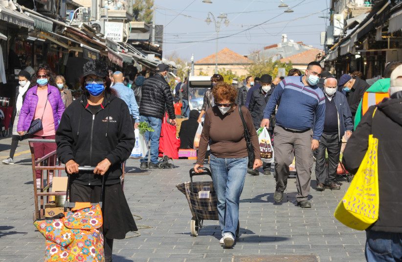 Israelis are seen walking in Jerusalem's Mahane Yehuda market amid the coronavirus pandemic, on January 6, 2021. (photo credit: MARC ISRAEL SELLEM/THE JERUSALEM POST)