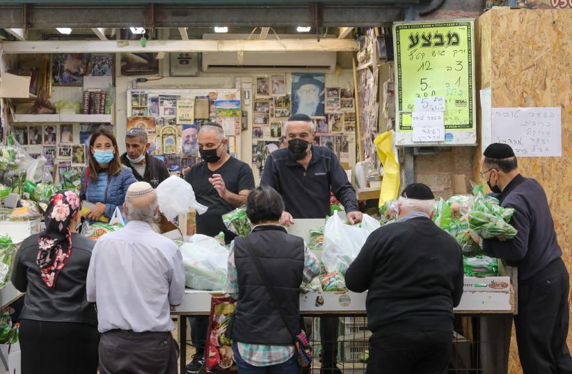 Israelis are seen shopping in Jeursalem's Mahane Yehuda amid the coronavirus pandemic, on January 6, 2021. (photo credit: MARC ISRAEL SELLEM/THE JERUSALEM POST)