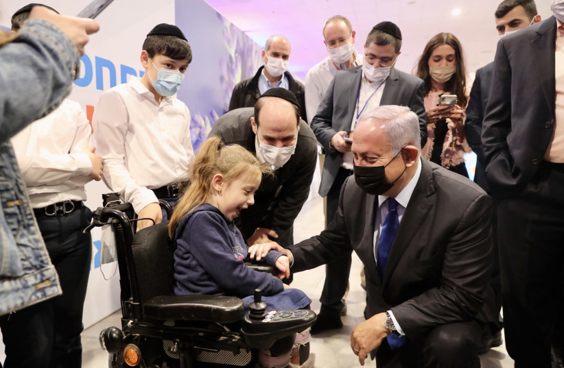 Prime Minister Benjamin Netanyahu is seen with young Ila Schwartz at the Meuhedet coronavirus vaccine center, on January 6, 2021. (photo credit: MARC ISRAEL SELLEM/THE JERUSALEM POST)