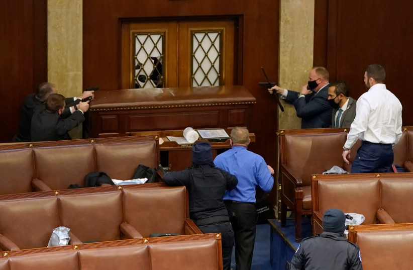 JANUARY 06: U.S. Capitol police officers point their guns at a door that was vandalized in the House Chamber during a joint session of Congress on January 06, 2021 in Washington, DC. Congress held a joint session today to ratify President-elect Joe Biden's 306-232 Electoral College win over Presiden (photo credit: DREW ANGERER/GETTY IMAGES)