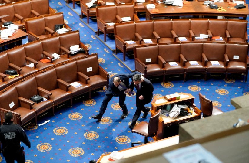 Members of Congress run for cover as protesters try to enter the House Chamber during a joint session of Congress on January 06, 2021 in Washington, DC to ratify President-elect Joe Biden's 306-232 Electoral College win over President Donald Trump. (photo credit: DREW ANGERER/GETTY IMAGES)