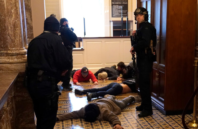 US Capitol Police stand detain protesters outside of the House Chamber during a joint session of Congress on January 06, 2021 in Washington, DC. Congress held a joint session today to ratify President-elect Joe Biden's 306-232 Electoral College win over President Donald Trump. A group of Republican  (photo credit: DREW ANGERER / GETTY IMAGES)