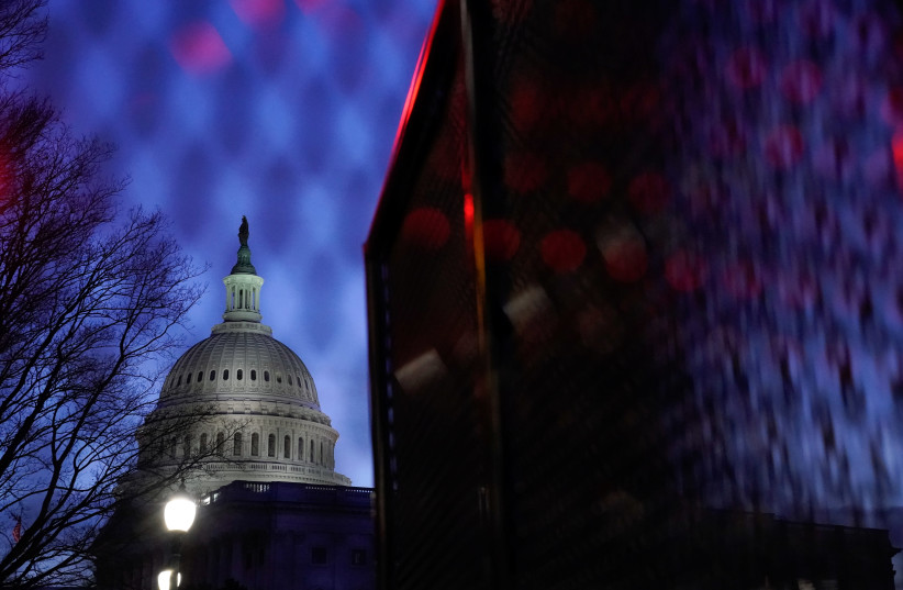 The US Capitol is seen behind heavy-duty security fencing the day after supporters of US President Donald Trump stormed the Capitol in Washington, US, January 7, 2021.  (photo credit: REUTERS/ERIN SCOTT)