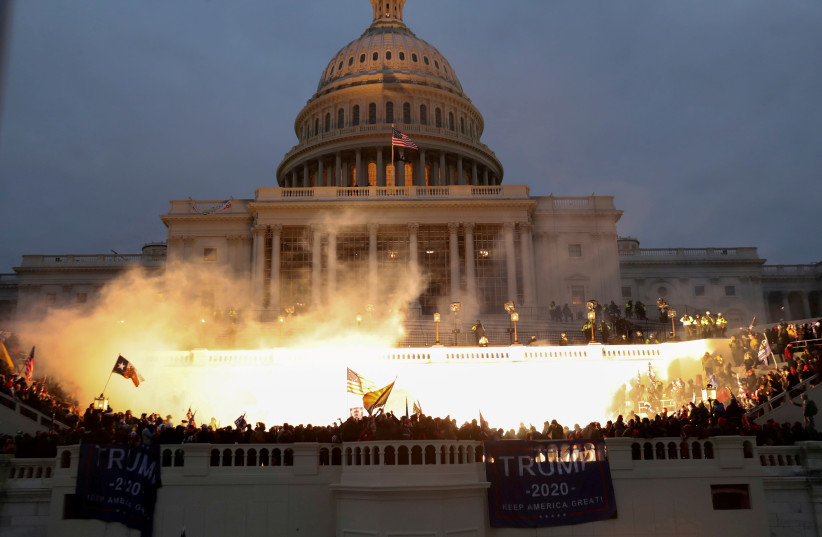 An explosion caused by a police munition is seen while supporters of US President Donald Trump gather in front of the US Capitol Building in Washington, US, January 6, 2021 (photo credit: REUTERS/LEAH MILLIS)
