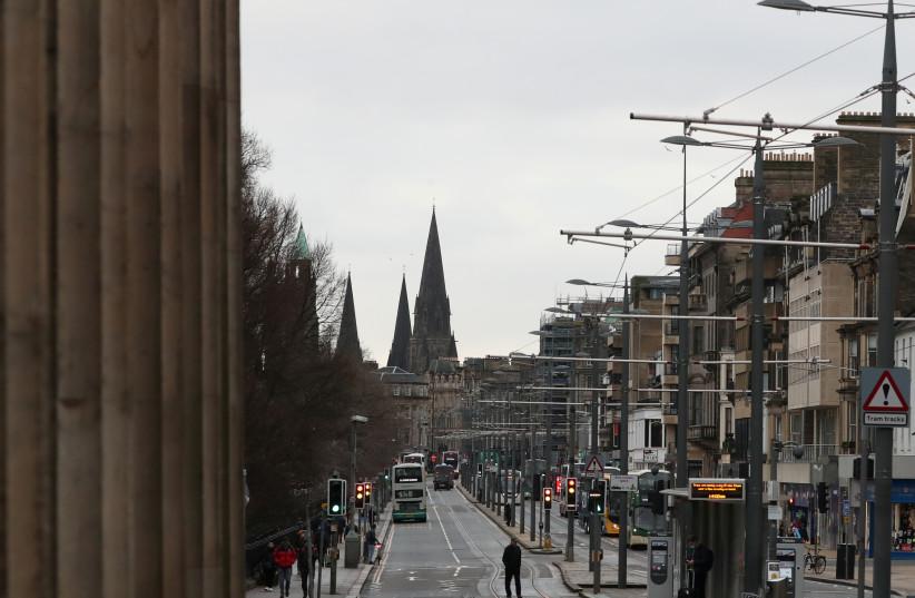 People walk on a street, amid the outbreak of the coronavirus disease (COVID-19), in Edinburgh, Scotland, Britain, January 5, 2021. (photo credit: RUSSELL CHEYNE/REUTERS)