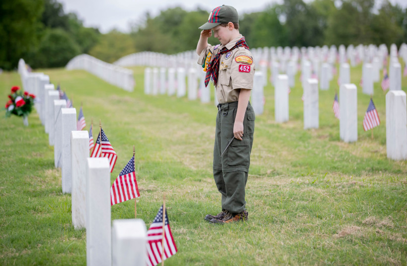 Cub Scout Colten Short, 10, of Arlington, salutes a grave after fixing a flag in front of a headstone ahead of the Memorial Day weekend at West Tennessee State Veterans Cemetery in Memphis, Tennessee, US May 19, 2020. (photo credit: MAX GERSH/THE COMMERCIAL APPEAL/USA TODAY NETWORK VIA REUTERS)