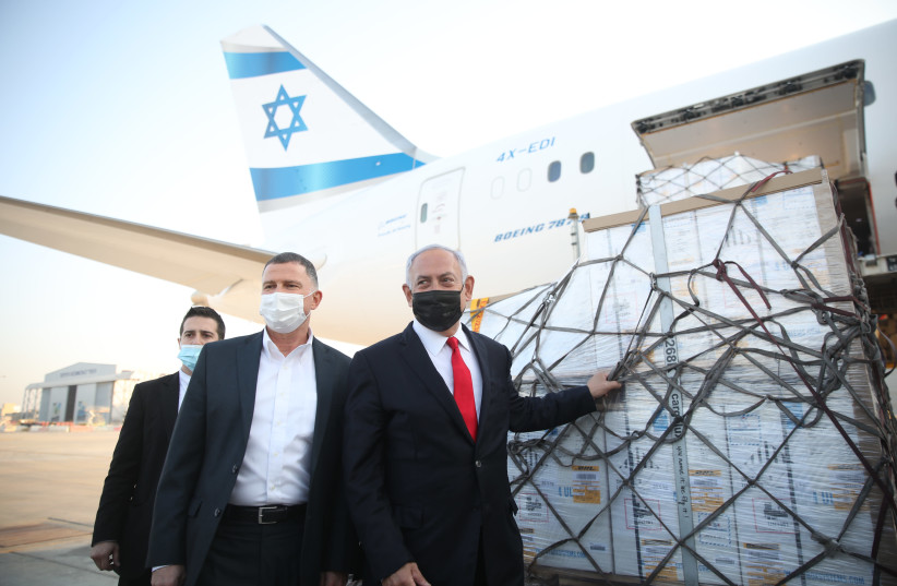 Prime Minister Benjamin Netanyahu and Health Minister Yuli Edelstein receive a shipment of Pfizer coronavirus vaccines, Sunday, January 10, 2020. (photo credit: MOTI MILROD)