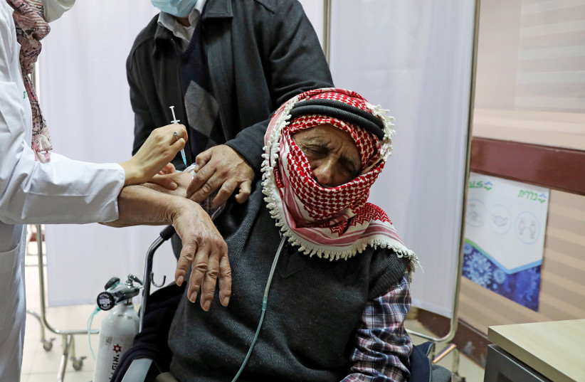 A Palestinian man is helped by his son as he receives a vaccination against the coronavirus disease (COVID-19) as Israel continues its national vaccination drive, in east Jerusalem December 23, 2020 (photo credit: REUTERS/AMMAR AWAD)