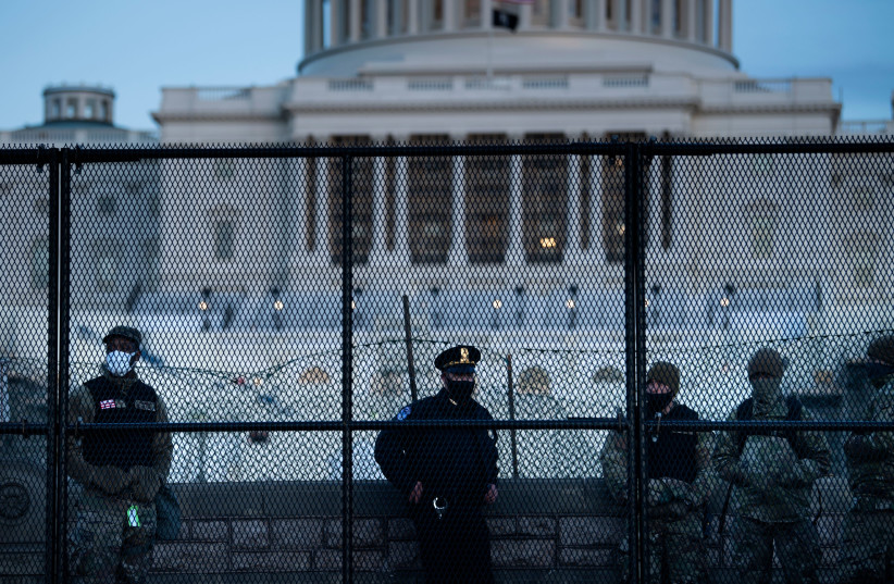 A Capitol police officer stands with members of the National Guard behind a crowd control fence surrounding Capitol Hill a day after a pro-Trump mob broke into the Capitol building, Jan. 7, 2021 (photo credit: BRENDAN SMIALOWSKI/AFP VIA GETTY IMAGE)