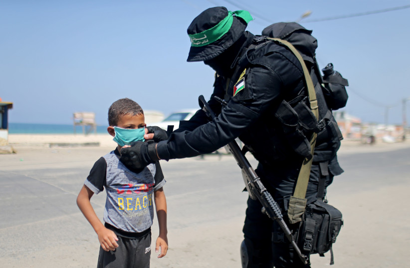 A Hamas militant hands out a protective face mask to a Palestinian boy during the coronavirus disease (COVID-19) outbreak, in the central Gaza Strip September 12, 2020. (photo credit: IBRAHEEM ABU MUSTAFA / REUTERS)
