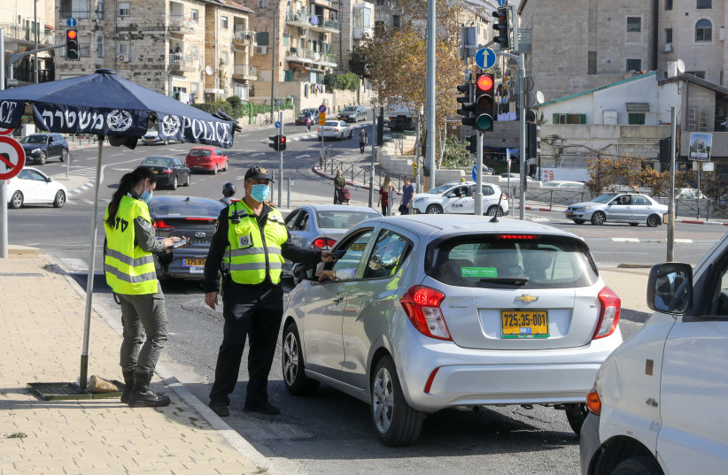 Police are seen checking drivers at a coronavirus checkpoint near Jerusalem's Gan Sacher amid lockdown, on January 12, 2021. (photo credit: MARC ISRAEL SELLEM/THE JERUSALEM POST)