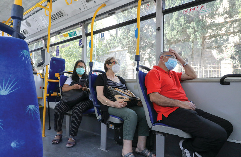 Passengers wear masks as they travel on a bus. (photo credit: MARC ISRAEL SELLEM)