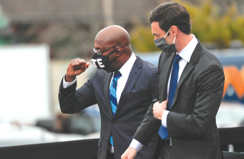 Newly-elected Georgia Senators Rev. Raphael Warnock and Jon Ossoff appear side by side ahead of the January 5 runoff election. (photo credit: MIKE SEGAR / REUTERS)