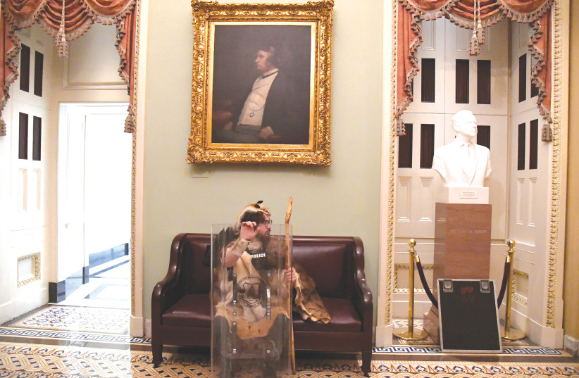 AARON MOSTOFSKY, a supporter of US President Donald Trump, takes a seat away from the action on the second floor of the US Capitol near the entrance to the Senate after breaching security defenses last week. (photo credit: MIKE THEILER/REUTERS)