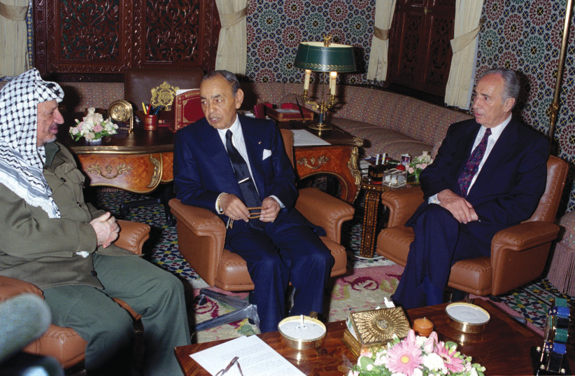 MOROCCO'S KING HASSAN II (center) speaks with PLO leader Yasser Arafat and foreign minister Shimon Peres in the King's Palace in Rabat, Morocco, 1995 (photo credit: REUTERS)