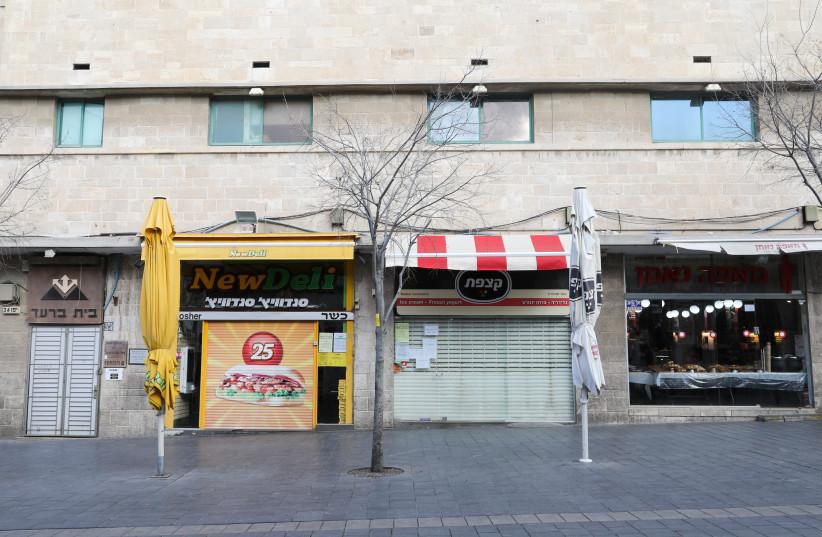Stores on Jerusalem's Jaffa Street are seen closed amid the ongoing coronavirus lockdown, on January 14, 2021. (photo credit: MARC ISRAEL SELLEM/THE JERUSALEM POST)