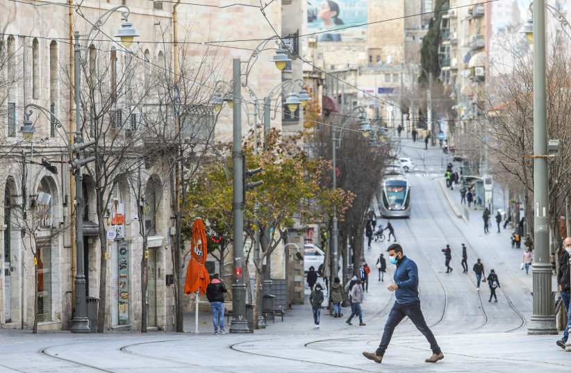 Israelis are seen walking along the Jaffa Street light rail tracks in Jerusalem amid the ongoing coronavirus lockdown, on January 14, 2021.. (photo credit: MARC ISRAEL SELLEM/THE JERUSALEM POST)