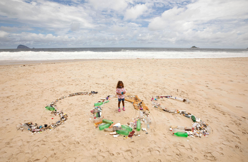 A young girl stands with collected trash sign reading SOS (photo credit: RICARDO GOMES/REUTERS)