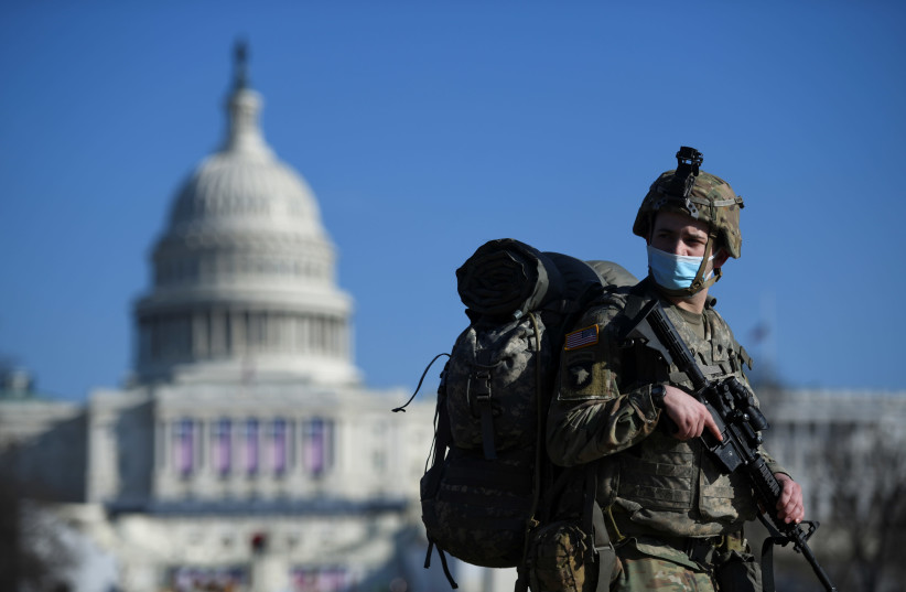 A member of the National Guard mounts guard near the US Capitol building, as the House of Representatives debates impeaching US President Donald Trump a week after his supporters stormed the Capitol building in Washington, US, January 13, 2021 (photo credit: REUTERS/BRANDON BELL)