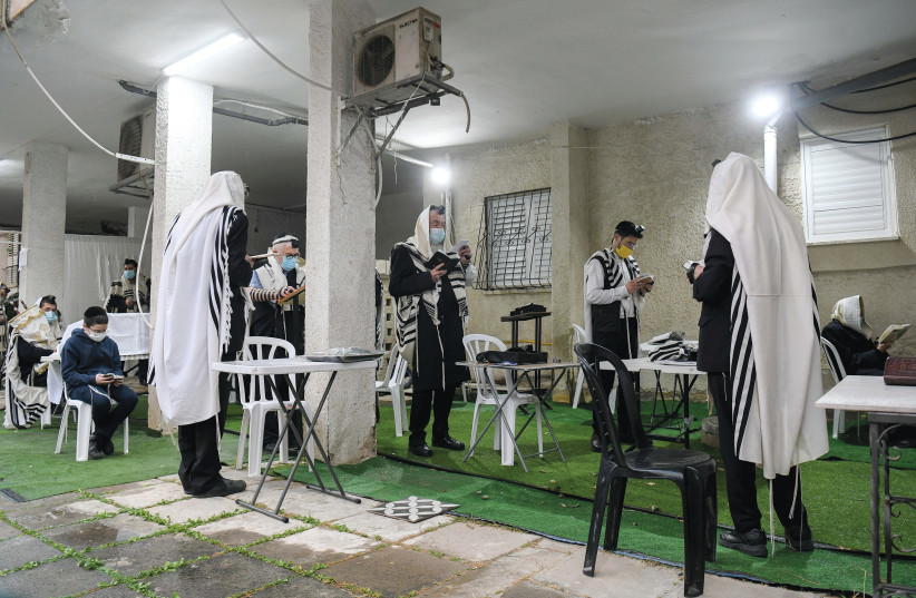 MEN PRAY outside during the third nationwide COVID-19 lockdown, in Bnei Brak on Thursday. (Yossi Zeliger/Flash90) (photo credit: YOSSI ZELIGER/FLASH90)