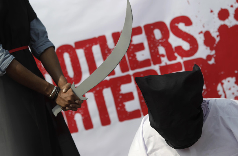 Members of Magic Movement, a group of young Bangladeshis, stage a mock execution scene in protest of Saudi Arabia beheading of eight Bangladeshi workers in front of National Museum in Dhaka October 15, 2011. Eight Bangladeshi migrants have been beheaded in the Saudi Arabian capital Riyadh in public  (photo credit: REUTERS/ANDREW BIRAJ)