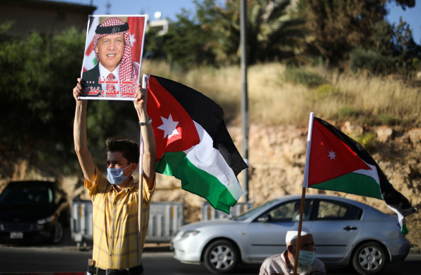 A protester holds a poster of Jordan's King Abdullah as he takes part in a human chain during a sit-in against the annexation of parts of the West Bank by Israel, in Amman, Jordan, June 27, 2020. (photo credit: REUTERS/MUHAMMAD HAMED)