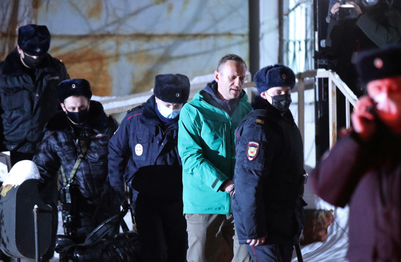Russian opposition leader Alexei Navalny is escorted by police officers after a court hearing, in Khimki outside Moscow, Russia January 18, 2021. (photo credit: EVGENY FELDMAN/MEDUZA/HANDOUT VIA REUTERS)