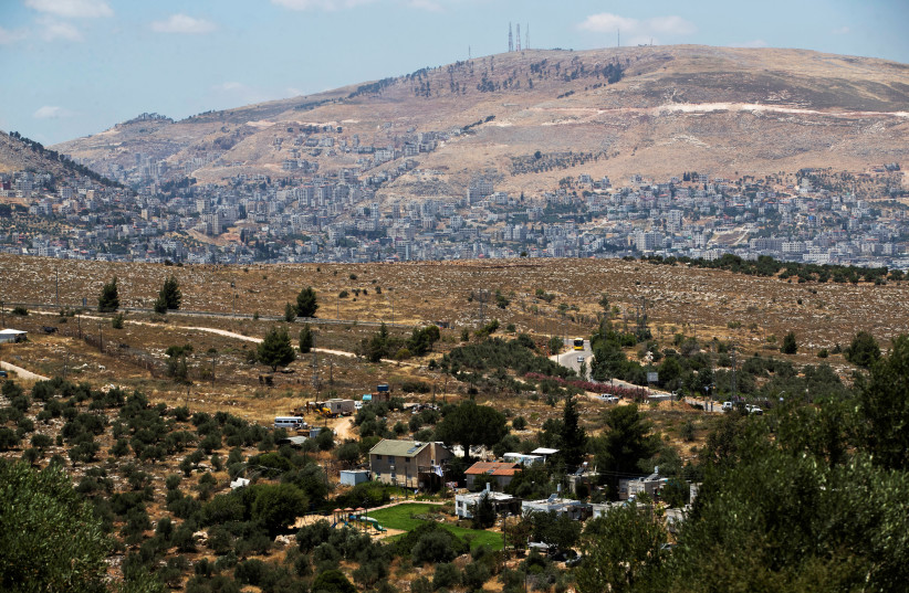 A general view picture shows a section of Itamar, a Jewish settlement, in the foreground as Nablus is seen in the background, in the West Bank June 15, 2020. (photo credit: RONEN ZVULUN/REUTERS)