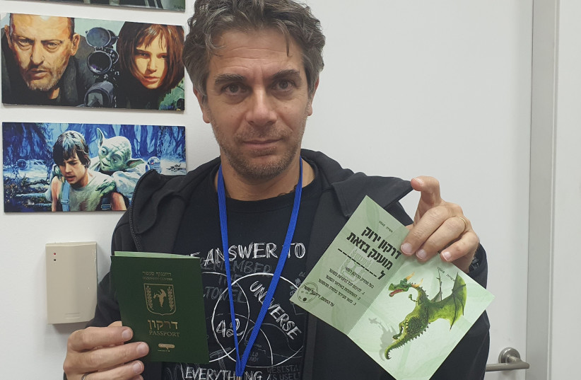 Dan Piltz receives his fake 'green passport', with a dragon on it, a play on words in Hebrew.  (photo credit: ALEX KAPLAN)