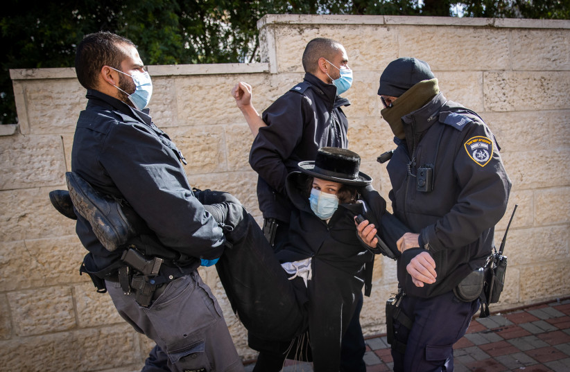 Police officers during a raid on a Yeshiva that is open in violation of the Covid-19 emergency regulations, at the Sanhedria Neighborhood in Jerusalem, January 19, 2021. (photo credit: YONATAN SINDEL/FLASH90)