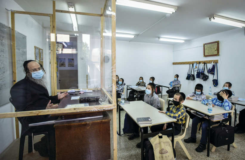 Ultra Orthodox students listen to their socially-distanced teacher at their school in Rehovot in September (photo credit: YOSSI ZELIGER/FLASH90)