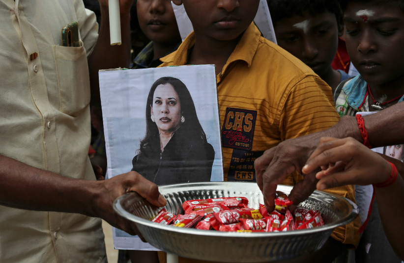 A man holds a placard with the photo of U.S. Vice President-elect Kamala Harris as another distributes sweets during the celebration on the day of her inauguration in the village of Thulasendrapuram, where Harris' maternal grandfather was born and grew up, in the southern Indian state of Tamil Nadu, (photo credit: REUTERS/P. RAVIKUMAR)