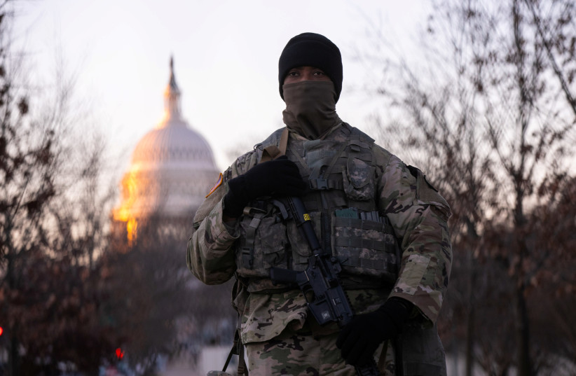 A member of the National Guard stands watch outside the U.S. Capitol at sunrise on President-elect Joe Biden's Inauguration Day in Washington, U.S., January 20, 2021. (photo credit: CAITLIN OCHS/REUTERS)