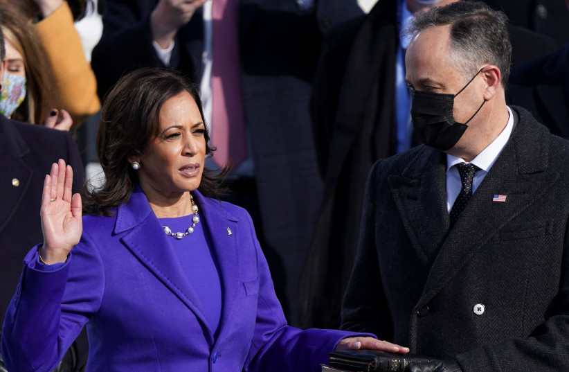 Kamala Harris is sworn in as U.S. Vice President as her spouse Doug Emhoff holds a bible during the inauguration of Joe Biden as the 46th President of the United States on the West Front of the U.S. Capitol in Washington, U.S., January 20, 2021. (photo credit: KEVIN LAMARQUE/REUTERS)
