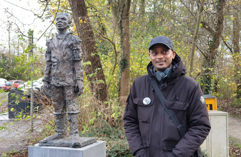 Sergio Berrenstein stands next to the statue of Elieser at the entrance to the Jewish cemetery in Ouderkerk aan de Amstel, the Netherlands on Nov. 20, 2020.  (photo credit: CNAAN LIPHSHIZ/JTA)
