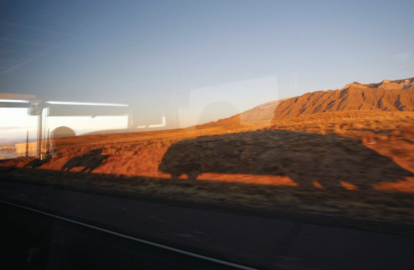 A BUS in Democratic presidential candidate Barack Obama's motorcade casts its shadow on a mountain, en route to Santa Fe in 2008. Cameron says her escape from loud New York to quieter Santa Fe inspired her book.  (photo credit: JASON REED/REUTERS)