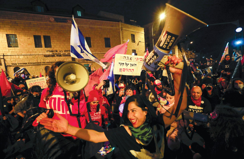 DEMONSTRATORS WITH megaphones in hand on Saturday night, January 16. (photo credit: OLIVIER FITOUSSI/FLASH90)