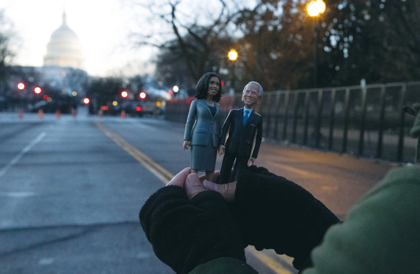 A supporter holds figures of US President Joe Biden and Vice President Kamala Harris outside a barrier in front of the US Capitol in Washington on January 20. (photo credit: CAITLIN OCHS/REUTERS)