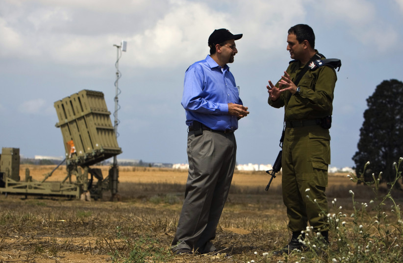 Dan Shapiro listens to an IDF officer as they stand next to an Iron Dome launcher in a field near the southern city of Ashkelon. (photo credit: REUTERS)