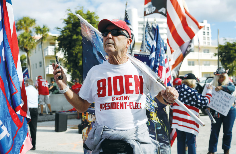 A SUPPORTER of former president Donald Trump holds a flag, in West Palm Beach, Florida, on Thursday. (photo credit: MARCO BELLO/REUTERS)