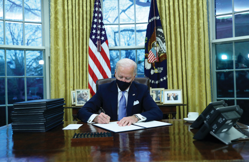 US PRESIDENT Joe Biden signs executive orders in the Oval Office of the White House on Wednesday, after his inauguration as the 46th president of the United States. (photo credit: TOM BRENNER/REUTERS)