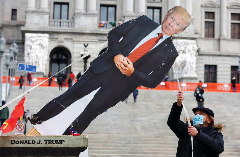 A MAN topples a cardboard cutout depicting former president Donald Trump outside the Pennsylvania State Capitol in Harrisburg, Pennsylvania, on Sunday. (photo credit: RACHEL WISNIEWSKI/REUTERS)
