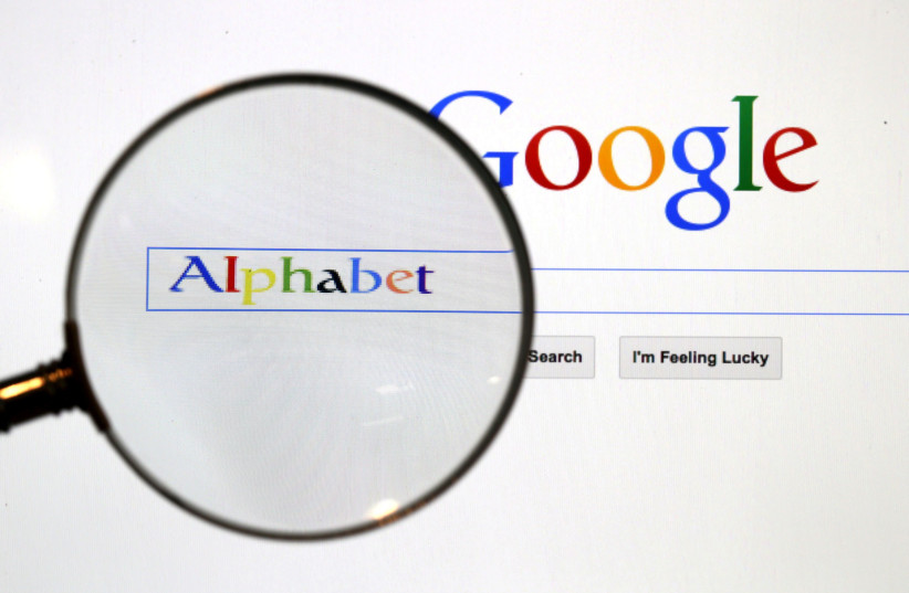 A Google search page is seen through a magnifying glass in this photo illustration taken in Berlin, August 11, 2015. (photo credit: REUTERS/PAWEL KOPCZYNSKI/FILE PHOTO)
