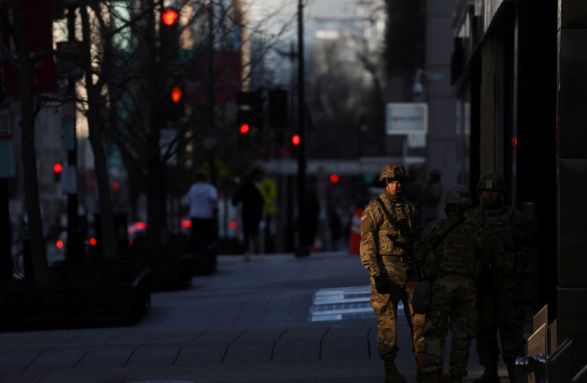 National Guard troops are seen near the secured zone set up for the inauguration of Joe Biden as the 46th President of the United States, near Black Lives Matter Plaza, in Washington DC, US, January 20, 2021.  (photo credit: REUTERS/LEAH MILLIS)