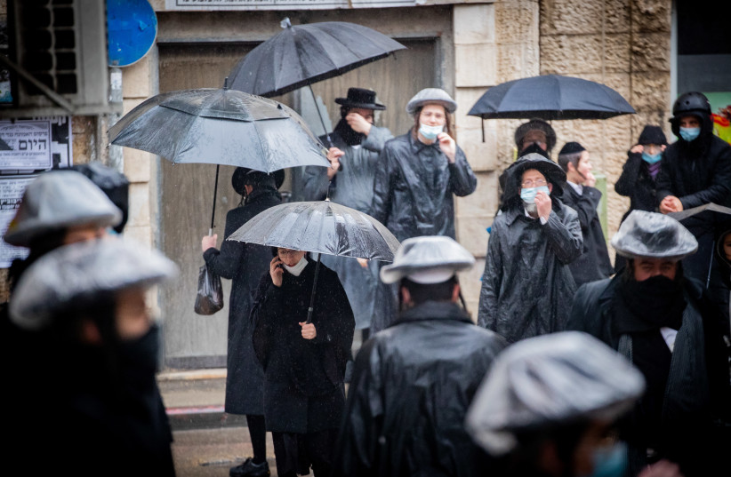 Ultra-Orthodox Jews seen in the street of the ultra-Orthodox neighborhood of Mea Shearim on a rainy day, January 18, 2021.  (photo credit: YONATAN SINDEL/FLASH 90)